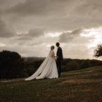 Photographie de jeunes mariés regardant vers l'horizon.